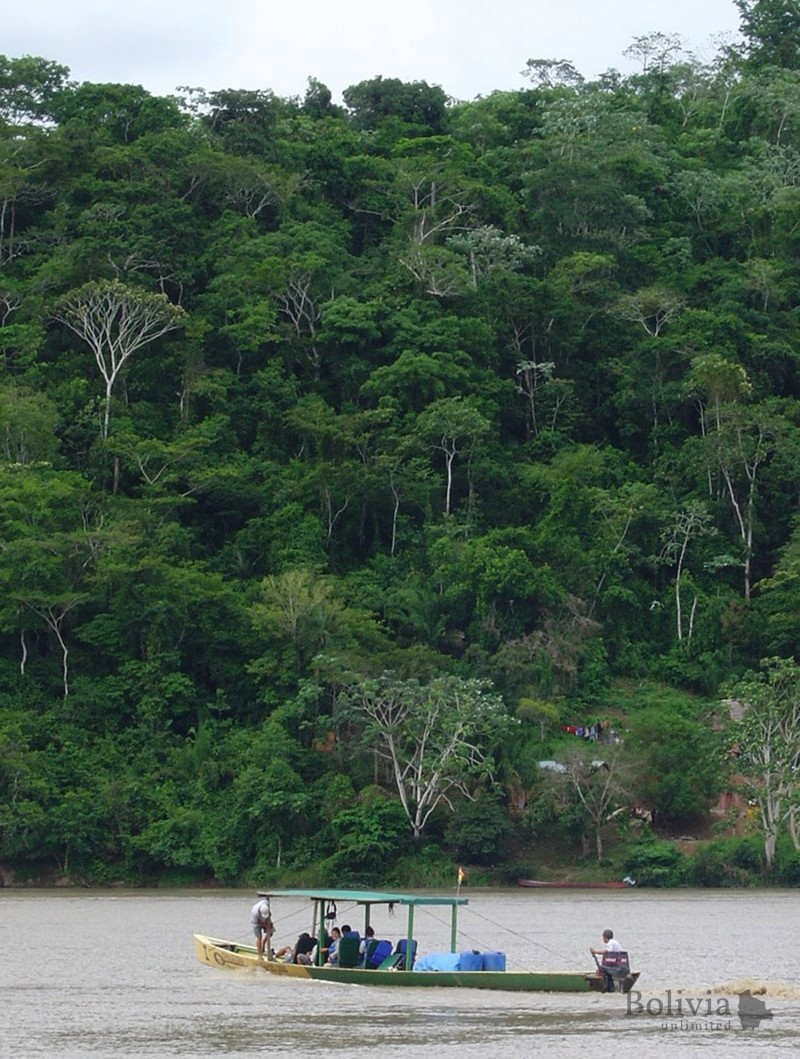 "Conservación Turismo - ""Locals navigating the river, surrounded by diverse tropical rainforest"""